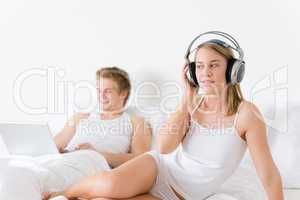 Young couple relax in bed with music and laptop