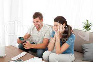 Happy man cutting his credit card with scissors with his girlfri