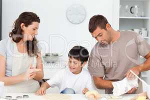 Caucasian family cooking biscuits together in the kitchen