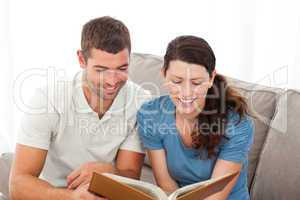 Lovely couple reading a book together on the sofa