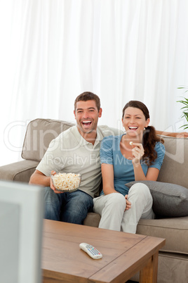 Cute couple eating pop corn while watching television on the sof