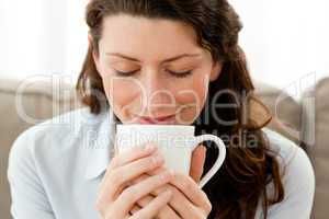 Cute businesswoman enjoying her coffee at home
