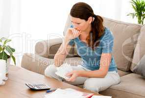 Stressed woman calculating her bills sitting on the sofa