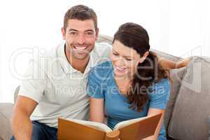 Pretty woman reading a book with her boyfriend on the sofa