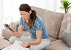 Nervous woman looking at her financial debts in the living room