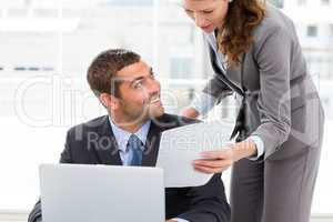Pretty businesswoman showing a paper to her colleague working on