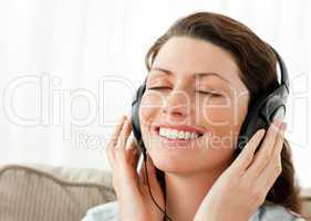 Pretty businesswoman relaxing with music sitting on the sofa