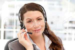 Pretty businesswoman with earpiece and looking at the camera