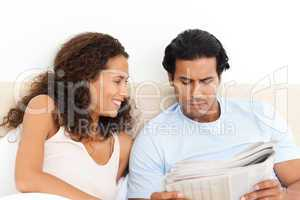 Happy woman looking at her serious boyfriend reading the newspap