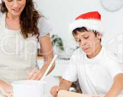 Cute boy preparing christmas biscuits with his mother
