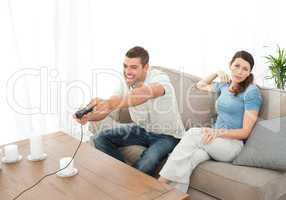 Desperate woman being bored while her boyfriend playing video ga