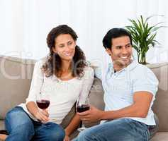 Lovely couple drinking red wine sitting on the sofa