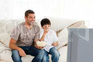 Happy man watching television with his son sitting on the sofa