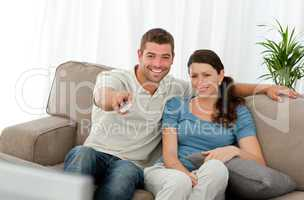 Happy man watching television with his girlfriend sitting on the