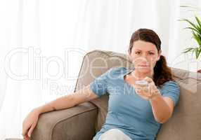 Charismatic woman watching television at home