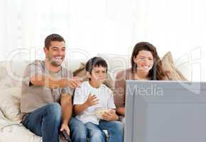 Family laughing while watching television together