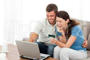 Happy couple looking at their accounts online sitting on the sof
