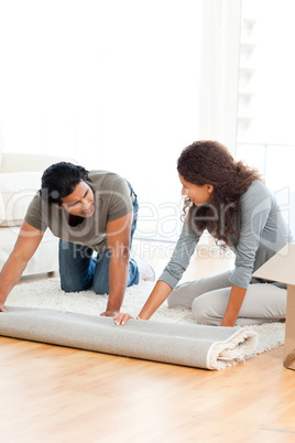Lovely couple rolling a carpet together in the living room