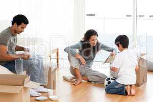 Happy family packing dishes together in their living-room