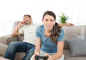 Serious woman playing video game while her boyfriend waiting for