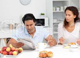 Concentrated couple reading the newspaper together during breakf