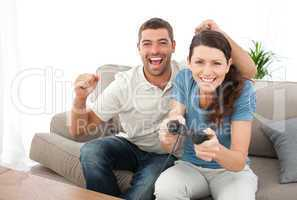Cheerful man encouraging his girlfriend playing video game