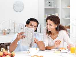 Happy couple reading the newspaper together during breakfast