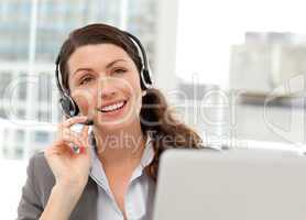 Thoughtful businesswoman talking on the phone while working on h
