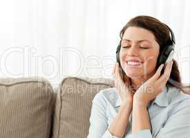 Happy businesswoman relaxing with music in the living-room