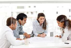Four charismatic architects looking at plans together