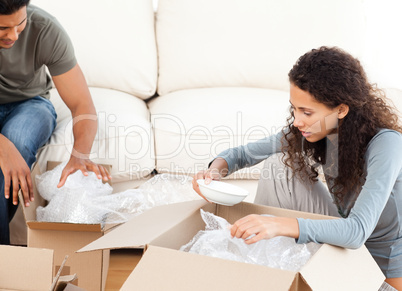 Happy woman packing glasses with her husband in the living-room
