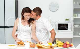 Affectionate man kissing his girlfriend while cutting bread for