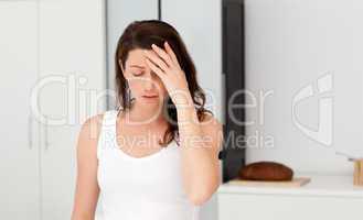 Exhausted woman having a headache in her bathroom