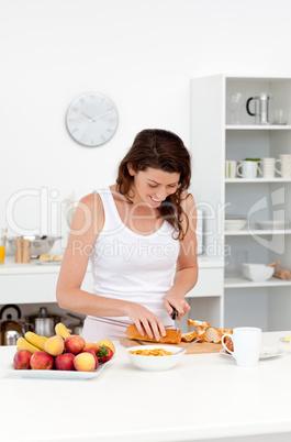 Joyful woman cutting bread for breakfast standing in the kitchen