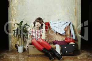 Young woman sits in a suitcase filled with clothes