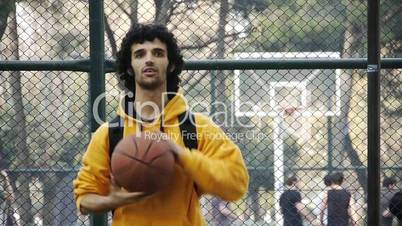 Young man play basketball ball turn on finger streetball sport game