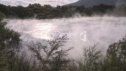 steam rises off a geotheral lake