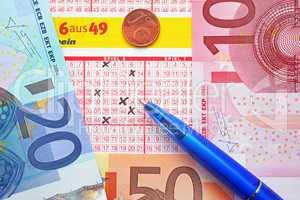 Lottoschein mit Euros und Kugelschreiber