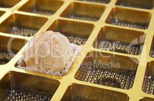 Weisse Praline in goldener Box