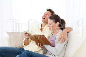 Man laughing while looking at a photo album with his girlfriend