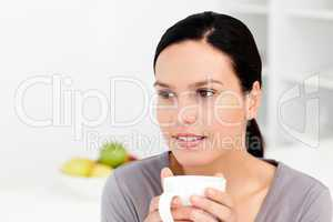 Pensive woman holding a cup of coffee sitting in the kitchen