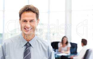 Happy businessman in the foreground while his team is working