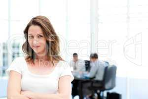 Beautiful businesswoman standing in front of her team while work