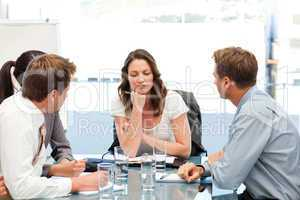 Thoughtful businesswoman at a table with her team