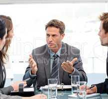 Severe manager talking to his team at a table