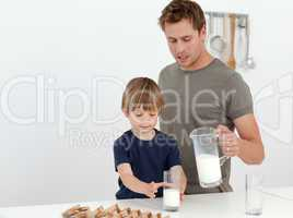 Handsome man giving milk to his son