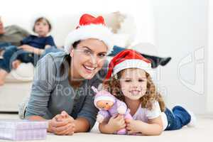 Happy mother and daugher at christmas lying on the floor