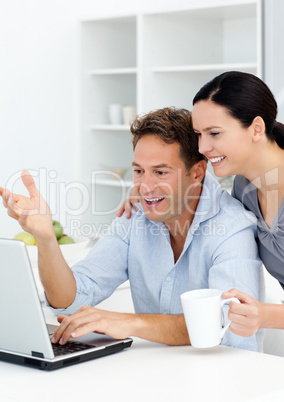 Lovely couple laughing while watching something on the laptop sc