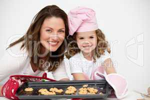 Lovely mother and daughter holding a plate with biscuits