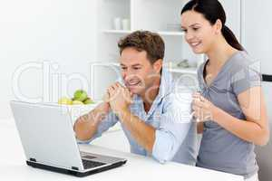 Happy couple looking at something on the laptop while drinking c